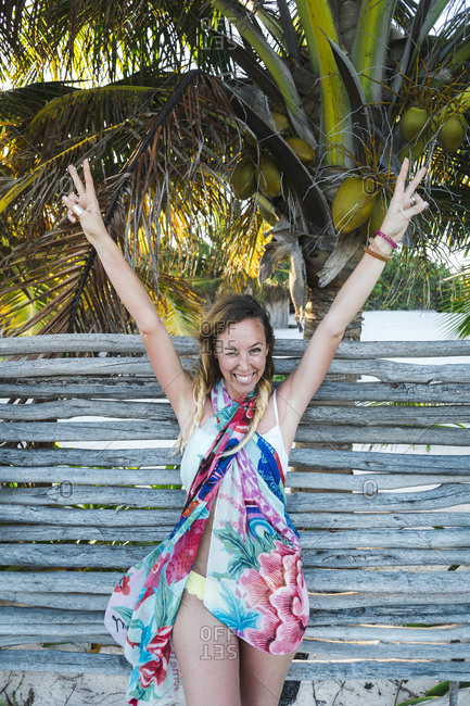 Cheerful woman peace gesturing with arms raised against wooden fence at beach