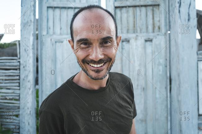 Happy mature man against wooden door at beach