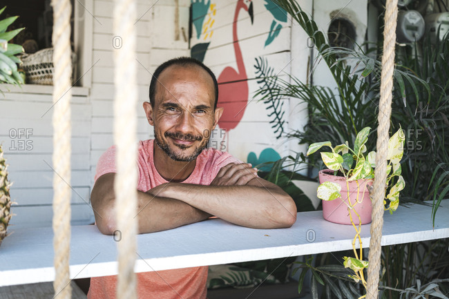 Smiling mature man leaning on plant shelf on his terrace