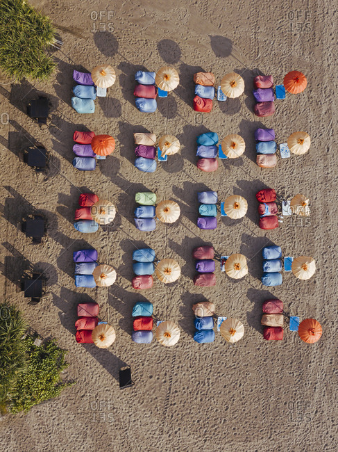 Aerial view of rows of umbrellas and deck chairs on empty Kuta Beach- Bali- Indonesia