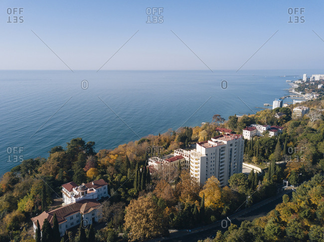 Russia- Krasnodar Krai- Sochi- Aerial view of edge of coastal city in autumn with clear line of horizon over Black Sea in background