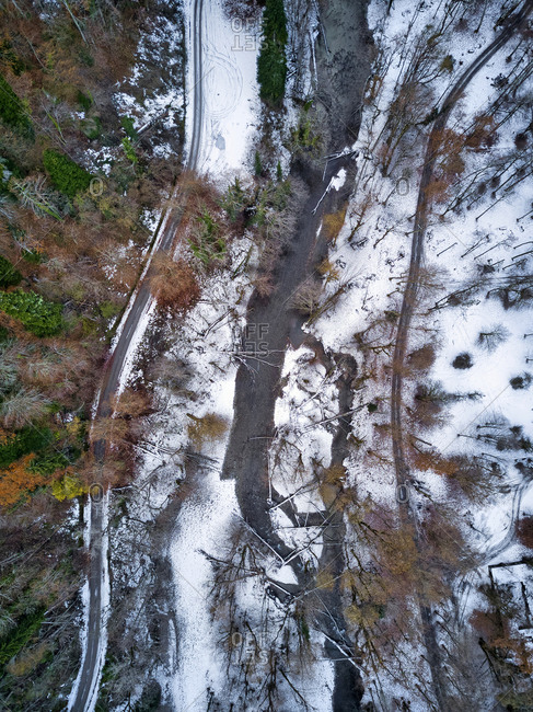 Aerial view of country road stretching through snow-covered landscape