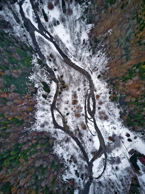 Aerial view of river flowing through snow-covered landscape