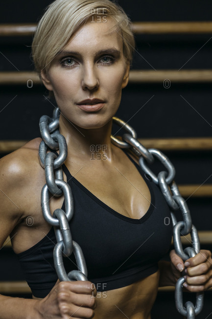 Blond sportswoman with chain at sport bars