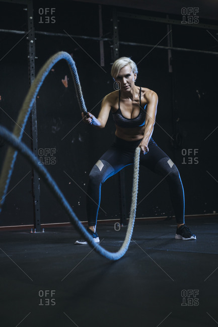 Blond sportswoman having workout with ropes