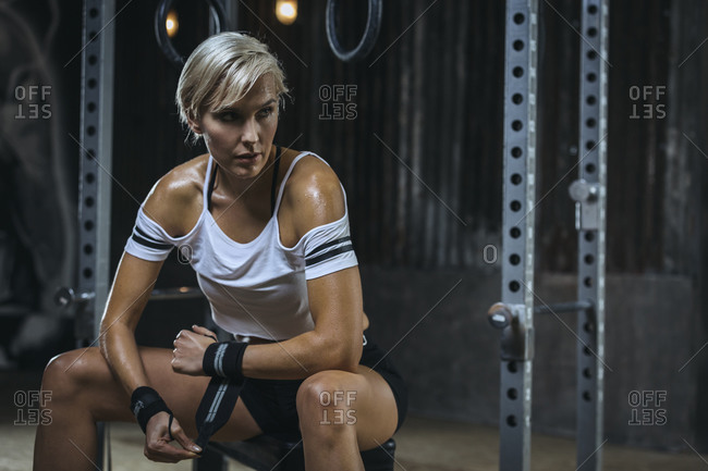 Portrait of blond sportswoman wearing white t-shirt and sweatband in gym