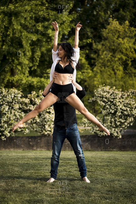 Dancer lifting female dancer with hands raised while practicing in back yard