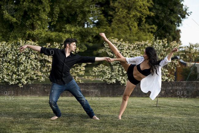 Dancer couple holding hand while dancing over grass in back yard