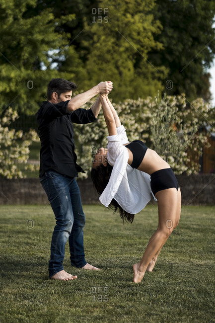 Male dancer holding hands of female dancer while standing on tiptoes and bending in back yard