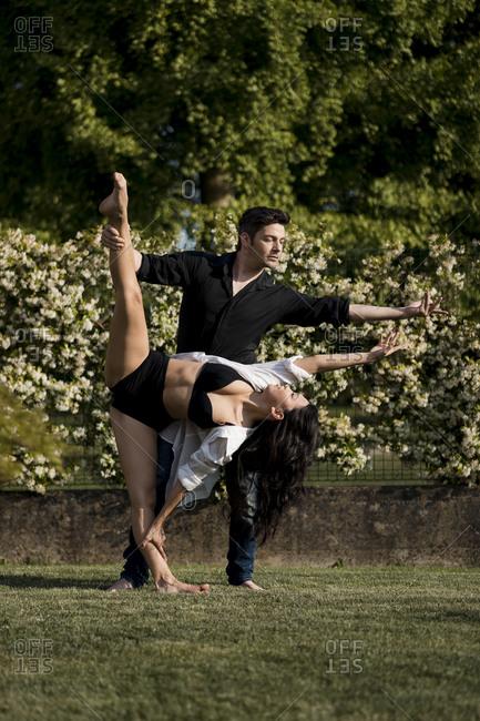 Heterosexual couple dancing with elegance in back yard during