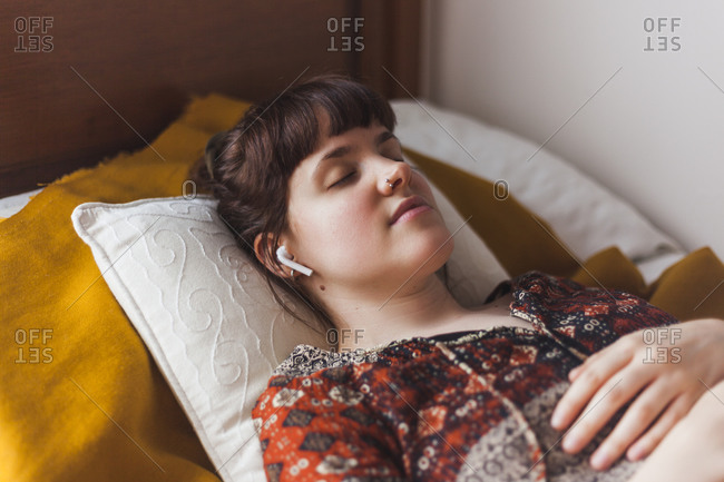 Young woman listening to guided meditation through wireless earphones while lying on bed