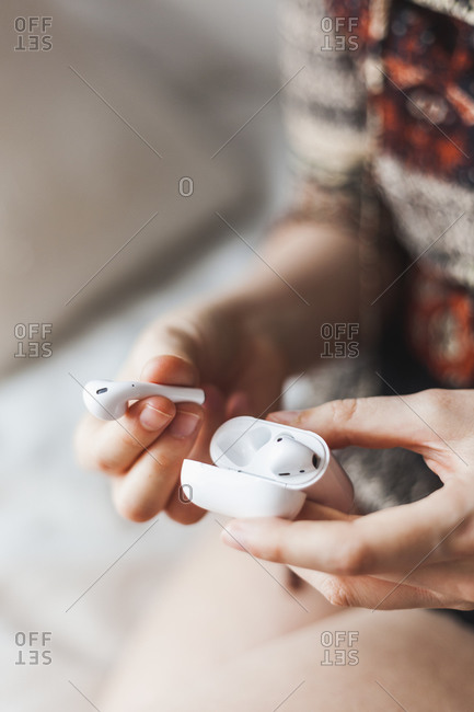 Woman's hands holding wireless headset