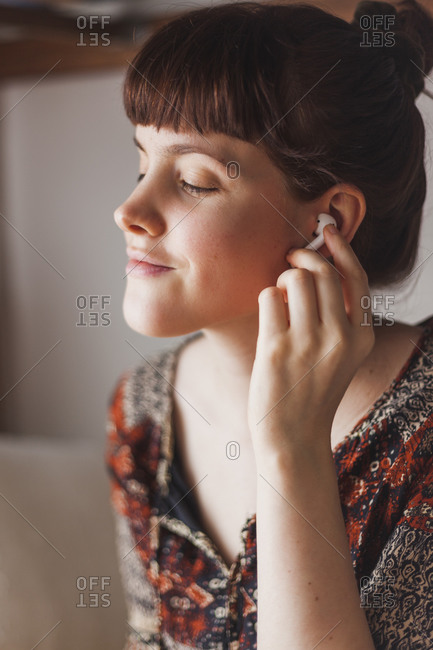 Young woman putting in wireless earphones