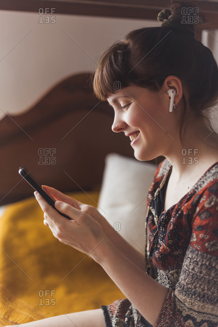Smiling woman making video call on smart phone while sitting in bedroom at home