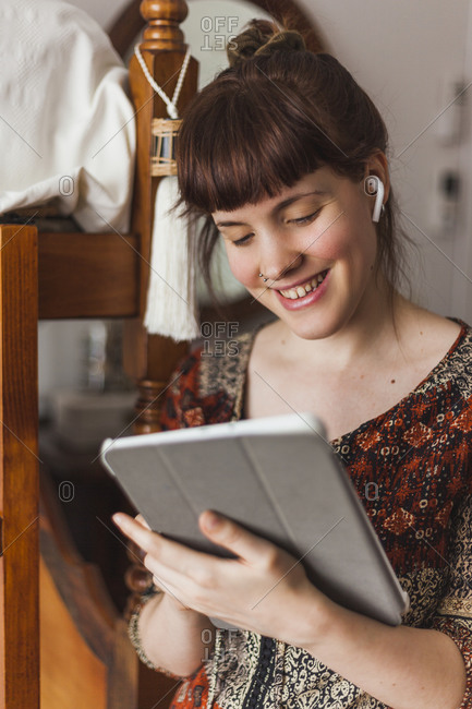 Beautiful woman reading news on digital tablet while listening to music through earphones at home