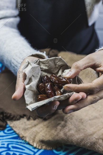 Hands of man picking up dates wrapped in paper