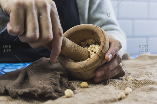 Hands of man grinding hazelnuts with mortar and pestle