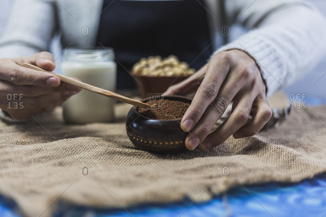 Hands of man taking spoon of cocoa powder