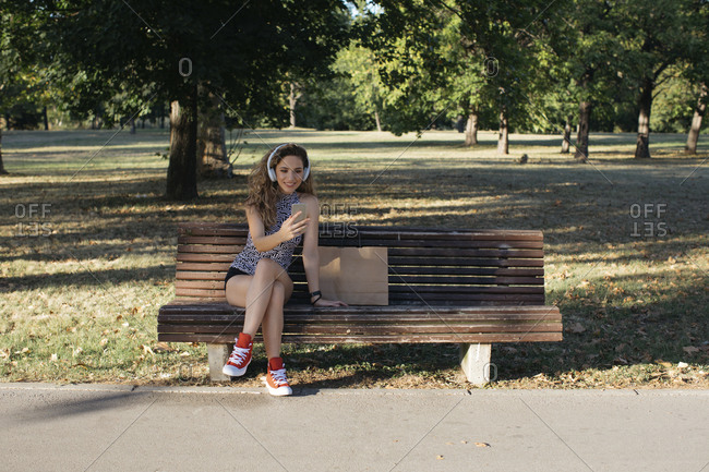 Smiling young woman on video call listening through headphones in public park