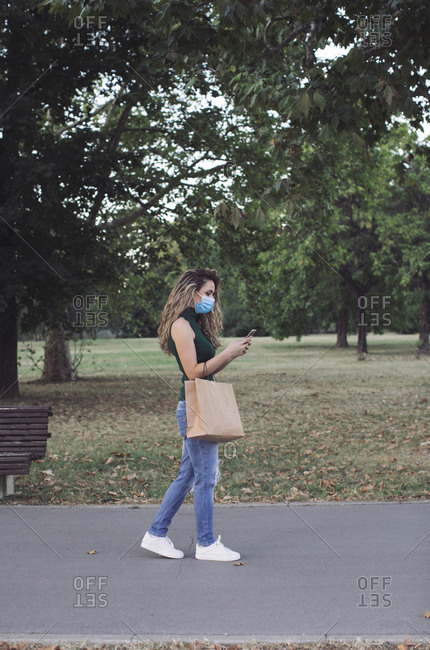 Young woman with paper bag using mobile phone while walking in public park during COVID-19