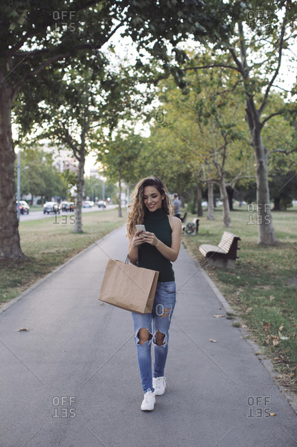 Happy young woman with paper bag using smart phone while walking in park