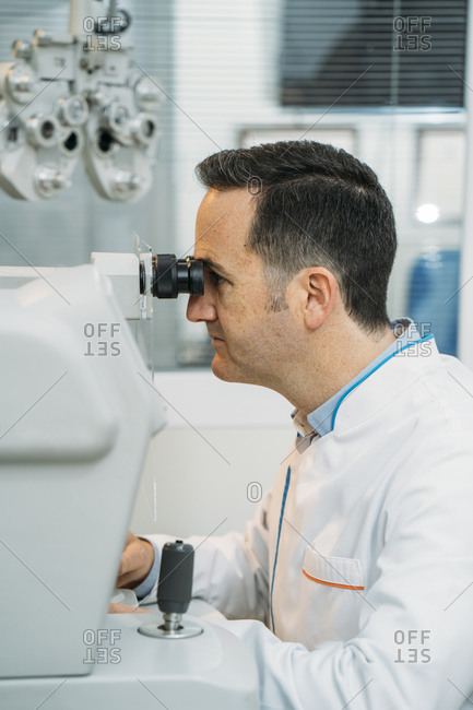 Male optometrist looking phoropter in clinic