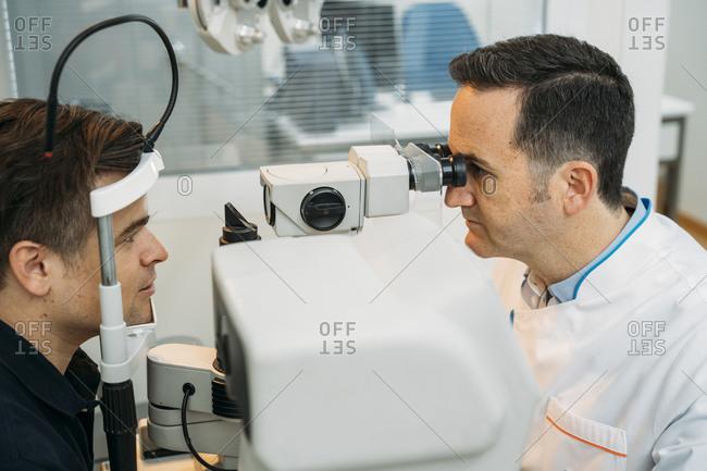 Mature optometrist examining patinet's eye through phropter in clinic