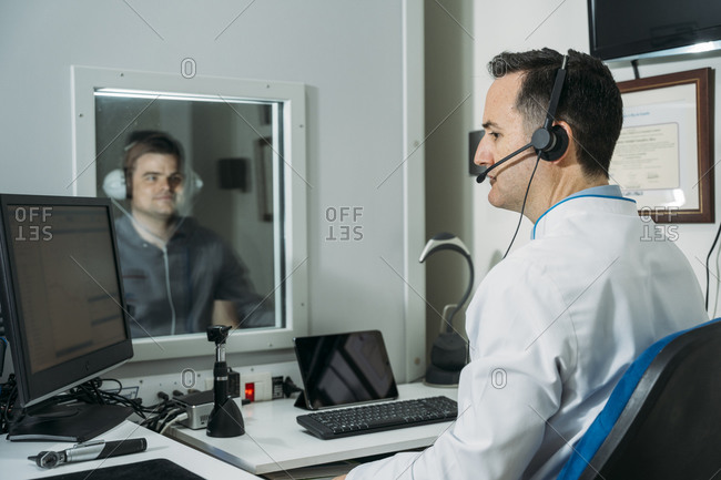 Male audiologist taking ear exam of patient wearing headphones in clinic