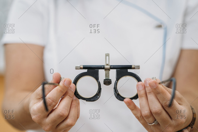 Female optometrist holding eye checking glasses at hospital