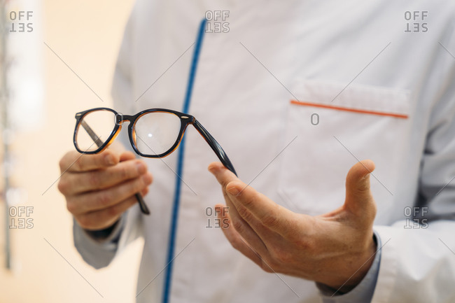Male optometrist holding eyeglasses in clinic