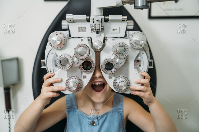 Cheerful girl with mouth open holding eye test equipment in clinic