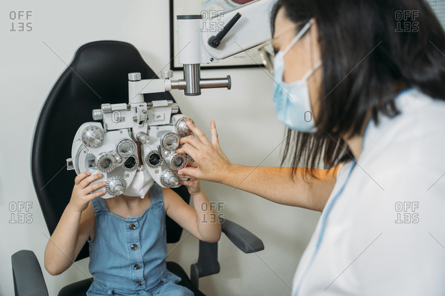 Female optometrist examining girls eyes through propther in clinic during COVID-19