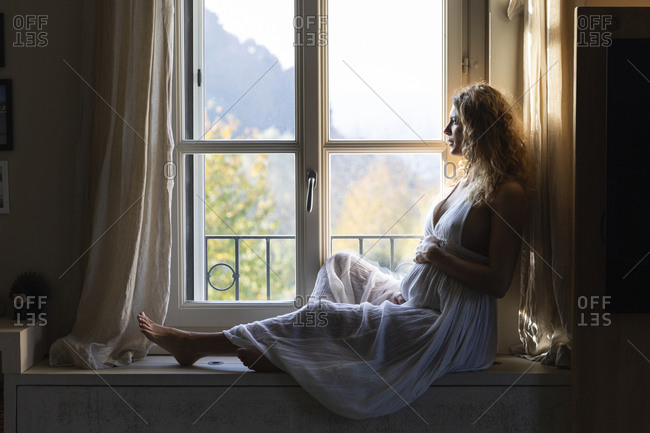 Thoughtful pregnant woman touching belly while looking through window at home