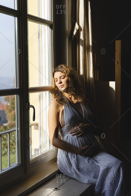 Pregnant woman with eyes closed touching belly while sitting on window seat at home