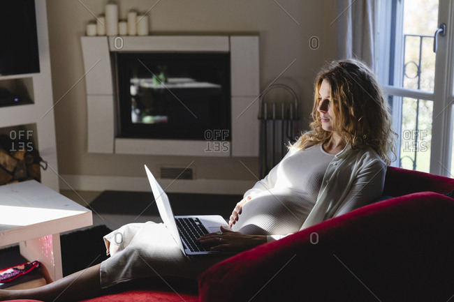 Pregnant freelancer using laptop while sitting on sofa in living room