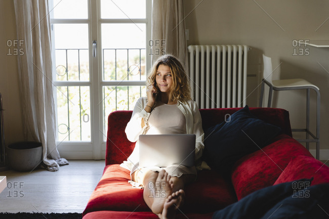 Pregnant freelancer with laptop talking on mobile phone at home