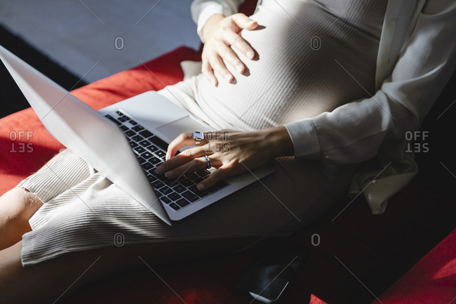 Pregnant freelancer typing on laptop at home