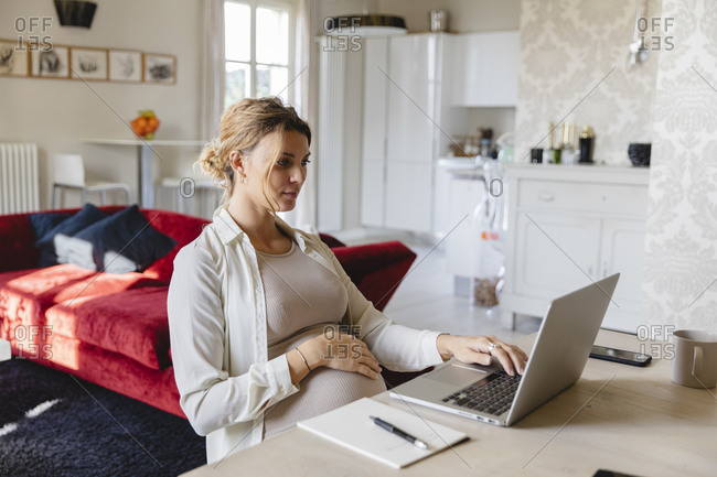 Pregnant businesswoman working on laptop at desk at home
