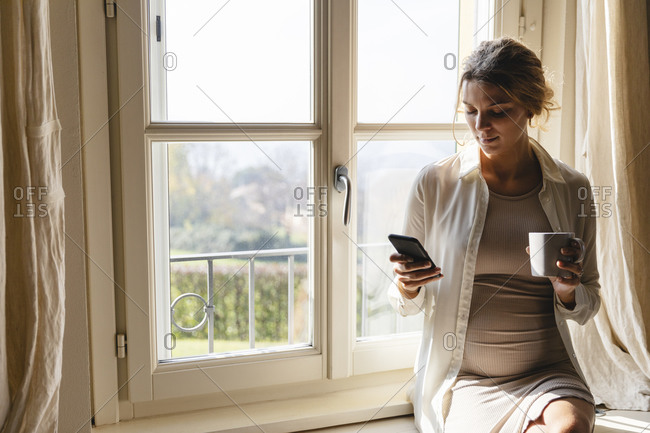 Young pregnant woman with coffee cup using smart phone against window at home