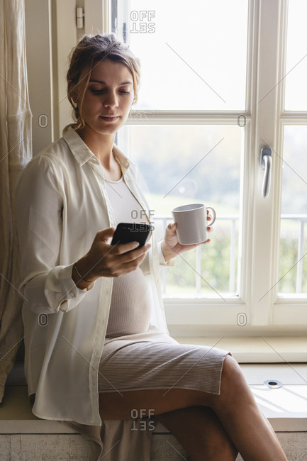 Pregnant woman with coffee cup using smart phone while sitting by window at home
