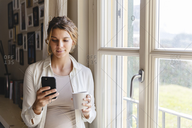 Young pregnant woman using smart phone by window at home