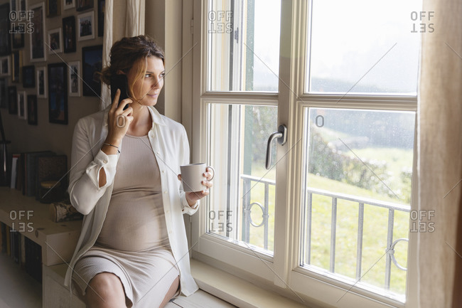Pregnant woman talking on mobile phone while looking through window