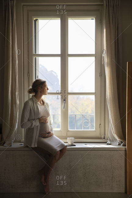 Pregnant woman with hands on stomach looking through window at home