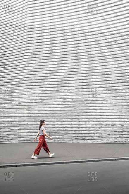 Woman wearing red pants walking on sidewalk by gray wall