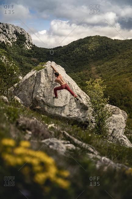 Boulderer climbing rock in mountain landscape