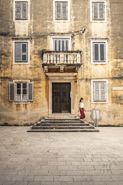 Woman descending steps at old building