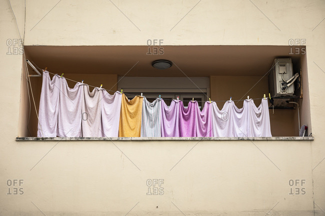 Row of colorful sheets on clothesline on balcony