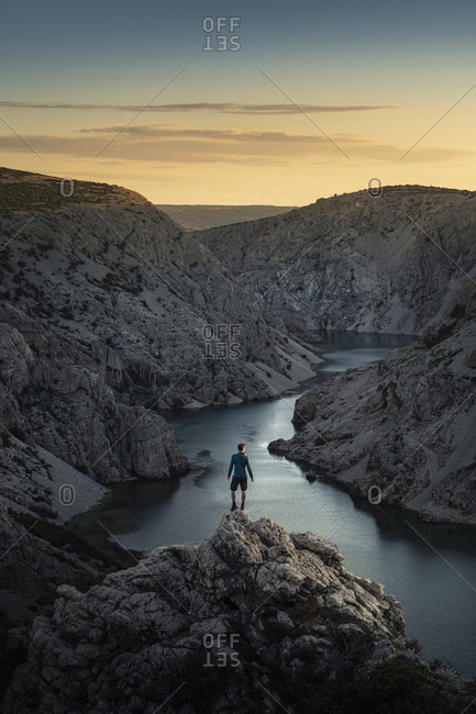 Man standing on rocks and looking at river in canyon at sunset