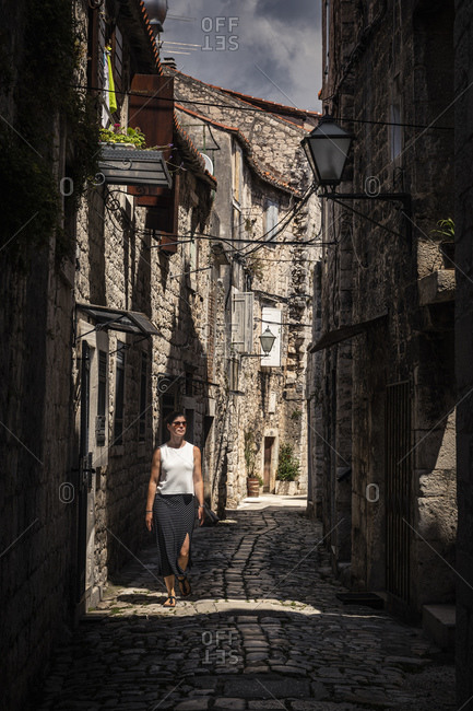 Woman walking on narrow alley in old town