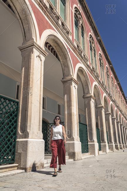 Croatia- Split- Woman passing by arcade on Republic Square